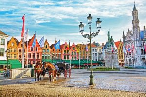 Horse-carriages-on-Grote-Markt-square-in-medieval-city-Brugge-at-morning-Belgium.-min
