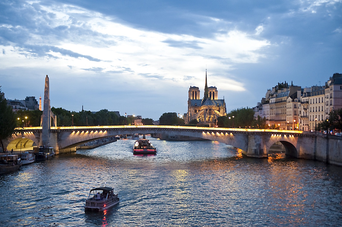 europe, france, paris, seine river at night with notre dame in background