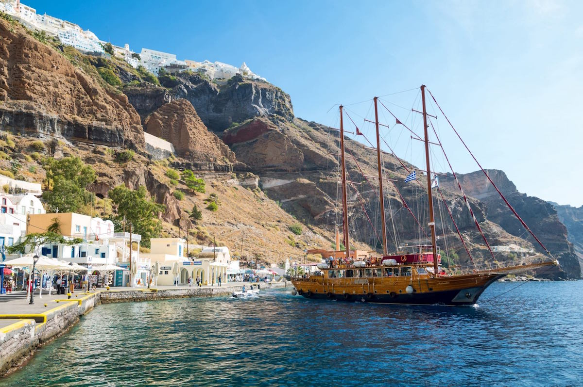 Greece, Santorini island, Fira, the old harbor with a sailing ship for tourists