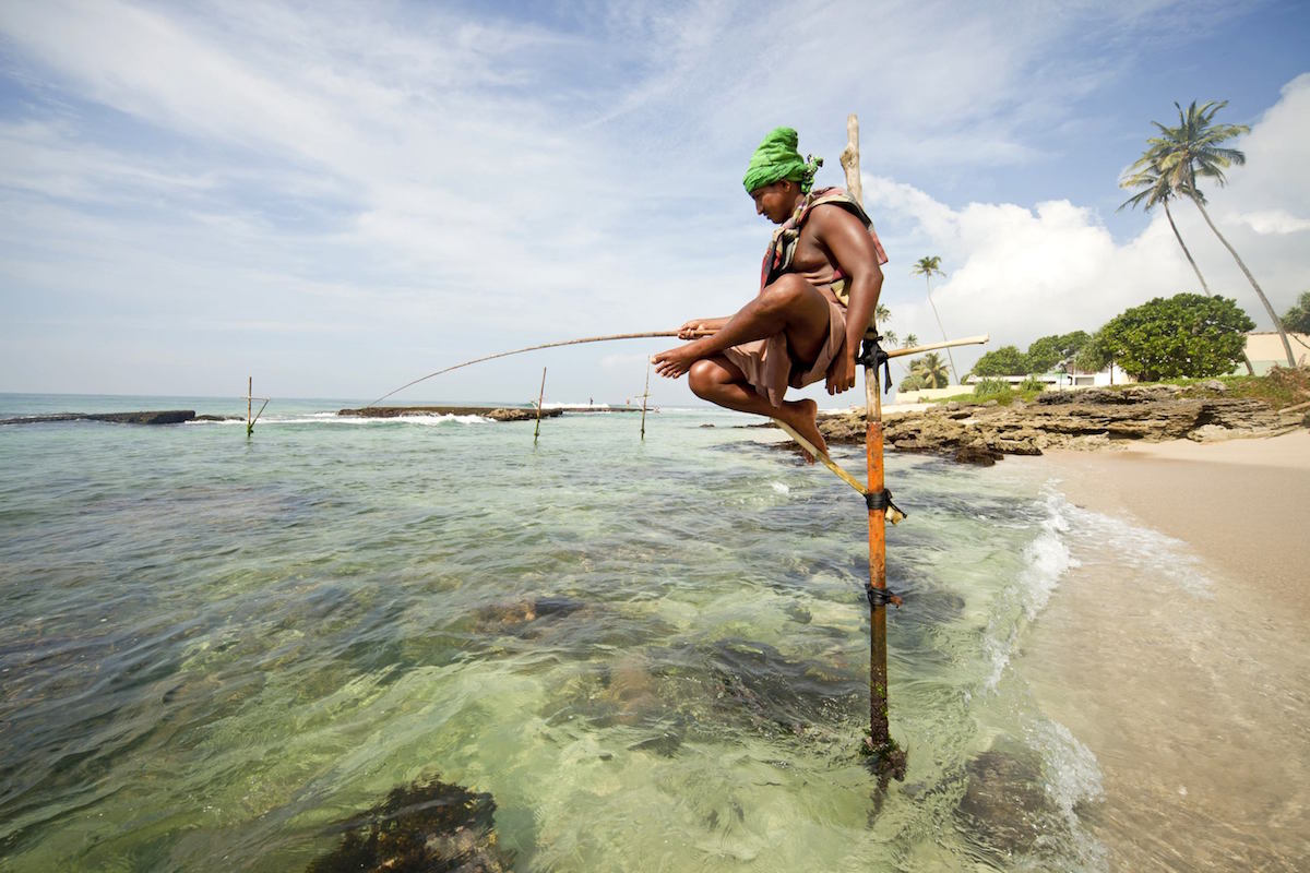 traditional stilt fishermen at work on the beach near Koggala, LKA, Sri Lanka