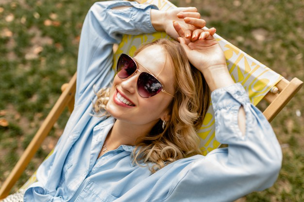 attractive-blond-smiling-woman-sitting-relaxed-deck-chair-stylish-outfit_285396-8242